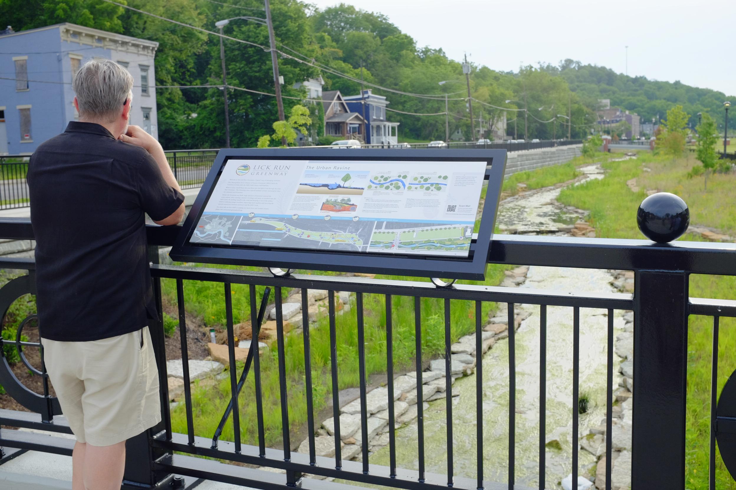 Man viewing an interpretive panel overlooking a stream.