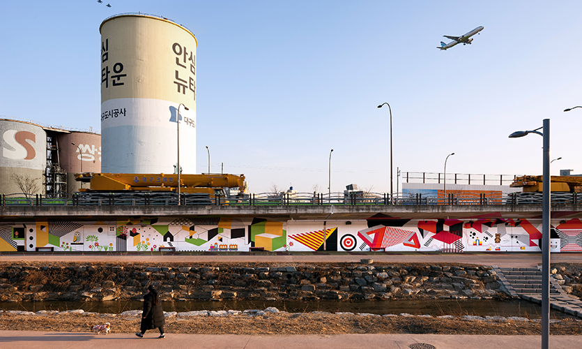 The Yulha Art Lounge is located in an area that is heavily restricted from developing due to its proximity to an air force base, an international airport, a river and bustling highway. (image: wide view showing industrial area)