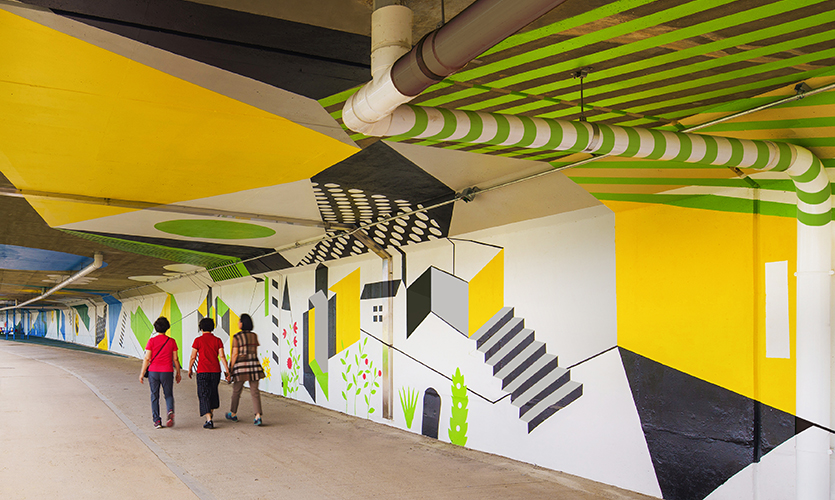 Happy Road consists of graphic designs that were directly inspired by views from within the neighborhood the space was designed for. (image: green and yellow representation of buildings)
