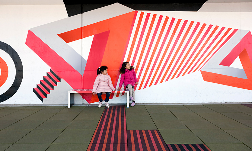 Children now have a safe cultural place to play in this neighborhood that is void of public parks. (image: two children sit on a bench behind vivid backdrop)