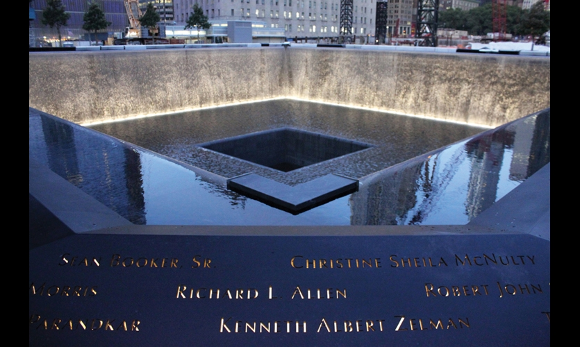 Outlining each tower's footprint is a bronze parapet, angled outward and bearing the names of the 2,983 victims. The names are cut through 1/2-in. bronze panels illuminated from below. (Photo: Joe Woolhead)