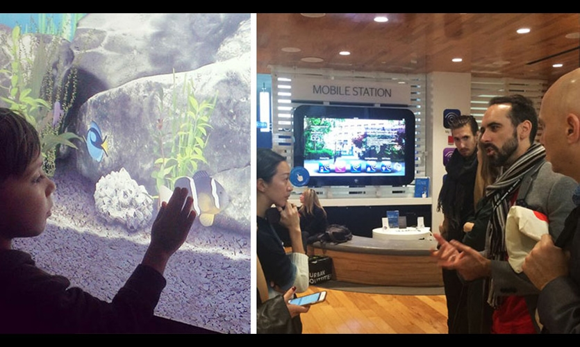 "The 2015 Xlab Interactive Retail Tour group at the Time Warner Cable Store, transformed by Reality Interactive into TWC's first ""Experience"" store. On the left, a digital fishtank that's purely for ambiance. On the right, interactve screens lets visitor locate free TWC public WiFi."