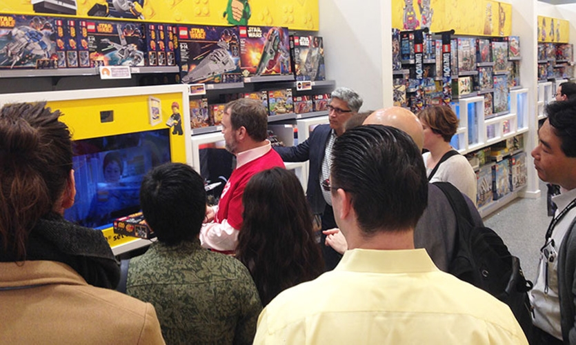 The 2015 Xlab Interactive Retail Tour group watches as Reality Interactive partner Craig Martin moves a box of Lego plane pieces in front of the screen. A fully built Lego plane magically appears on top of the box through augmented reality.