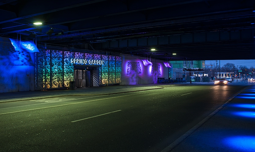 "As one approaches the underpass, large letterforms over the portals spell out ""Spring Garden"" as colorful lighting gently pulses through the leafy portal screens, drawing the gaze inward and through."
