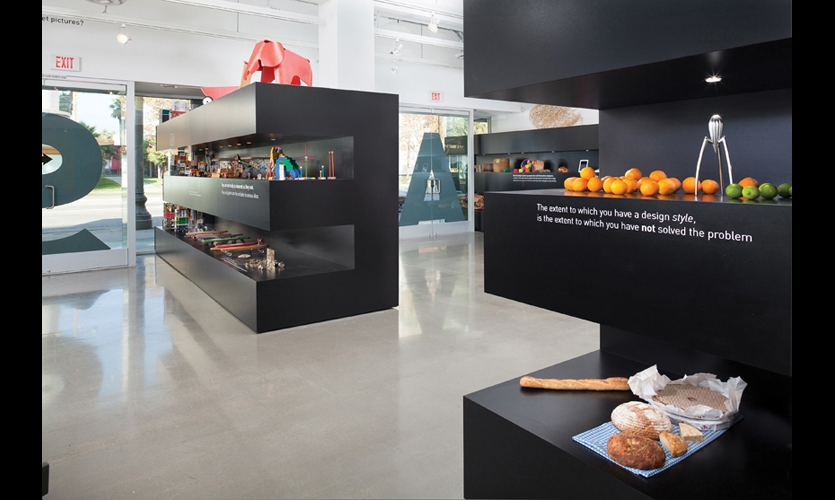 "The exhibition's primary identification does double duty: the ""E's"" stretch 18 ft. into the exhibition space in the form of black-painted, MDF shelving, becoming the primary mode of object display. (Photo: Clark Dugger)"