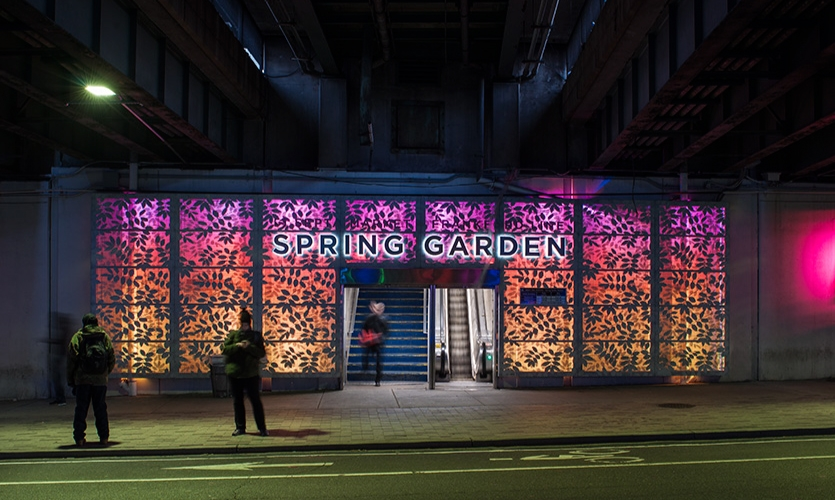 A series of Wisteria-festooned, 1.5-foot-deep by 13-foot-high by 50-foot-long, perforated aluminum panels form the portals in the center of the underpass, framing the doorways to the SEPTA elevated train station.