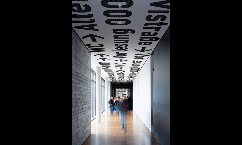 """At the University of Applied Sciences Osnabrück (2004), Uebele created a """"sky"""" of wayfinding information with black type and arrows occasionally interspersed with red """"clouds."""" (Photo: Andreas Körner)"""