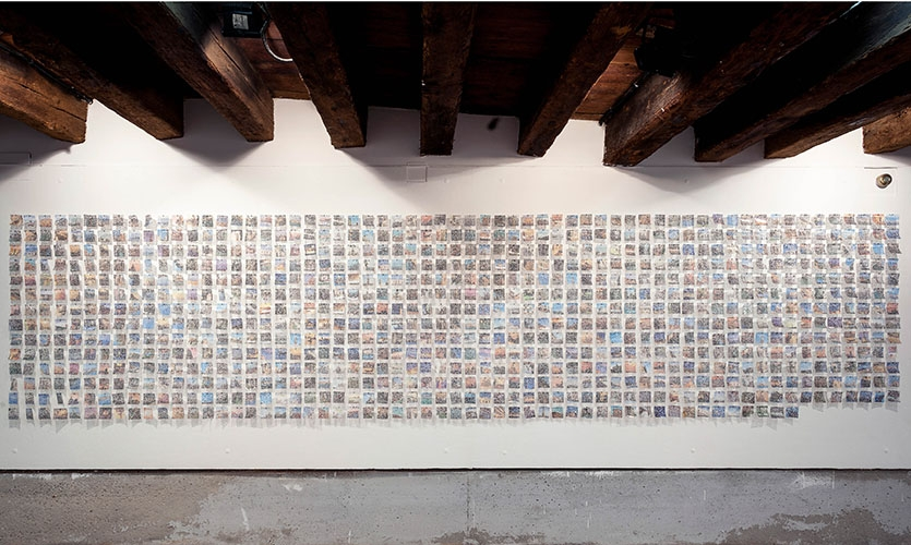 Installation detail – 847 unique views of Venice cut from commercial postcards and punctured.