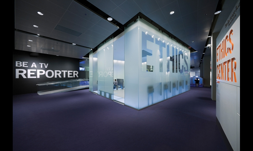 "Positioned literally and symbolically below the glass Media Tower, the Ethics Gallery glows ""like a beacon for truth."" The glass is sandblasted with the wording left clear, and 10 interactive stations allow visitors to test their own ethics."