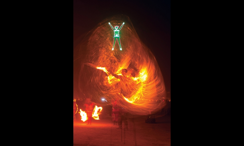 Fire dances are a prelude to the Burning Man climax. This dancer is on stilts as he spins his fire sticks. (Photo: George Post © 2012)