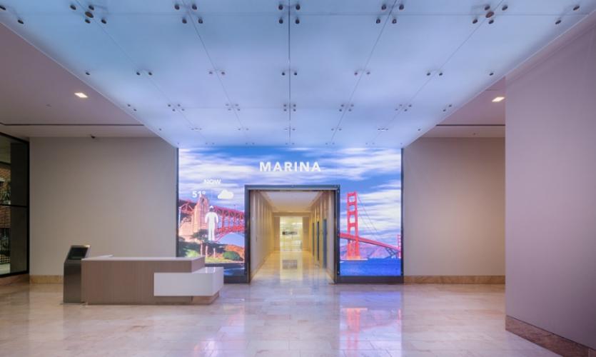A covering of etched architectural glass diffuses the LED light over the display, creating a seamless appearance from street to lobby.