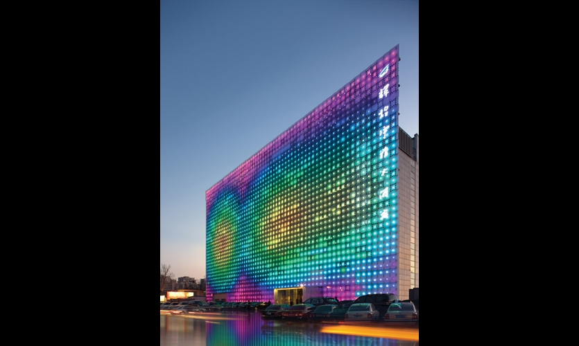 At dusk, the GreenPix Zero Energy Media Wall begins its low-resolution light show.