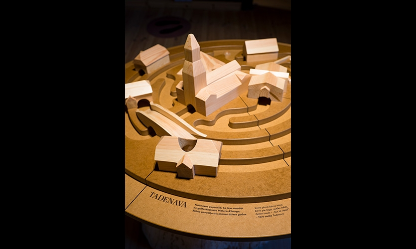 A rotating 3-D wooden map contains different places of Rainis's childhood. Visitor rotates the table that way traveling through those places with the help of the ball.