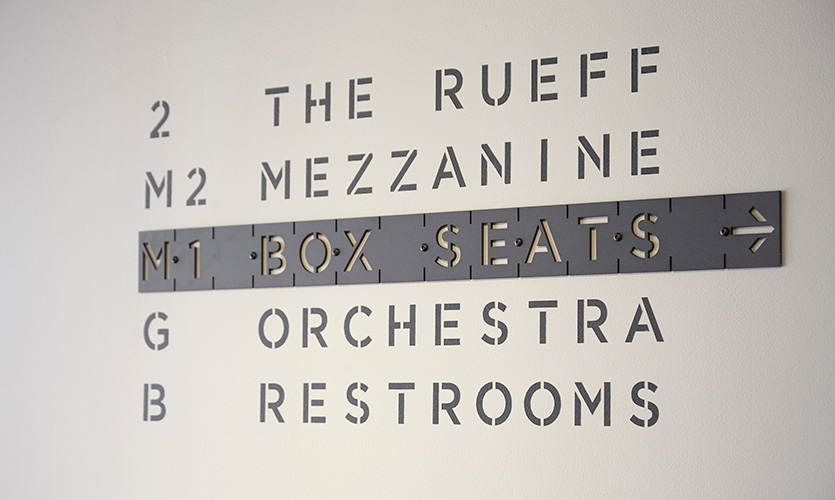 The lettering's charcoal color scheme connects with the raw, exposed concrete found in the lobby's interior walls and flooring.