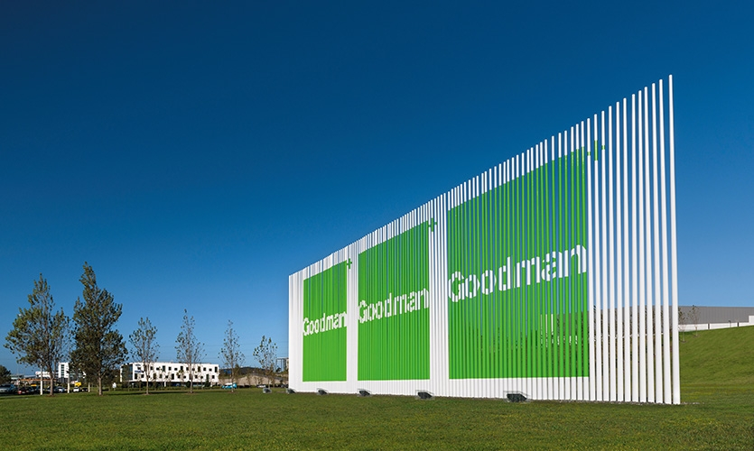 """Kinetic Grasses"" uses poles to create a visual fence. The sculptures delineate the site's boundary and incorporate the Goodman logo, which is revealed on approach and dissolves as viewers pass it."