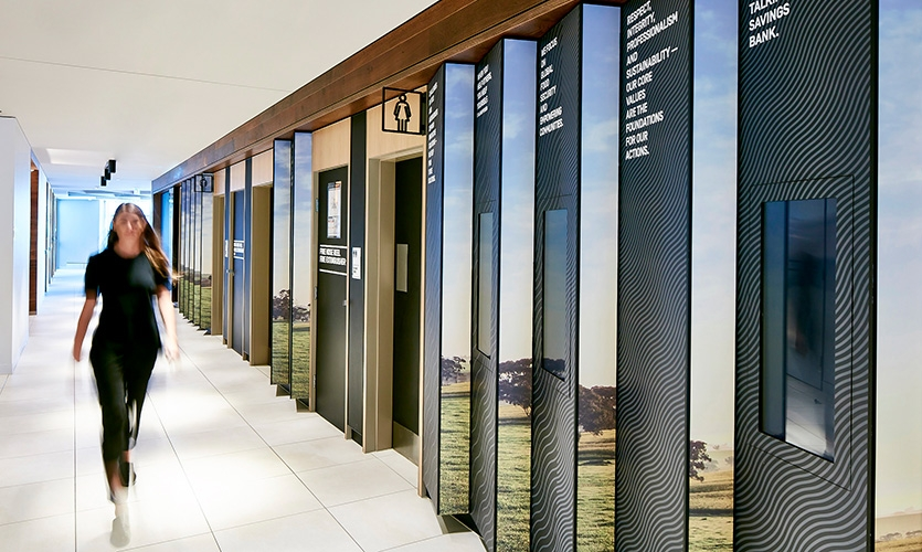 Animating a main access corridor, a lenticular wall installation displays rural imagery alongside digital screens that tells the various stories of Rabobank's customers.