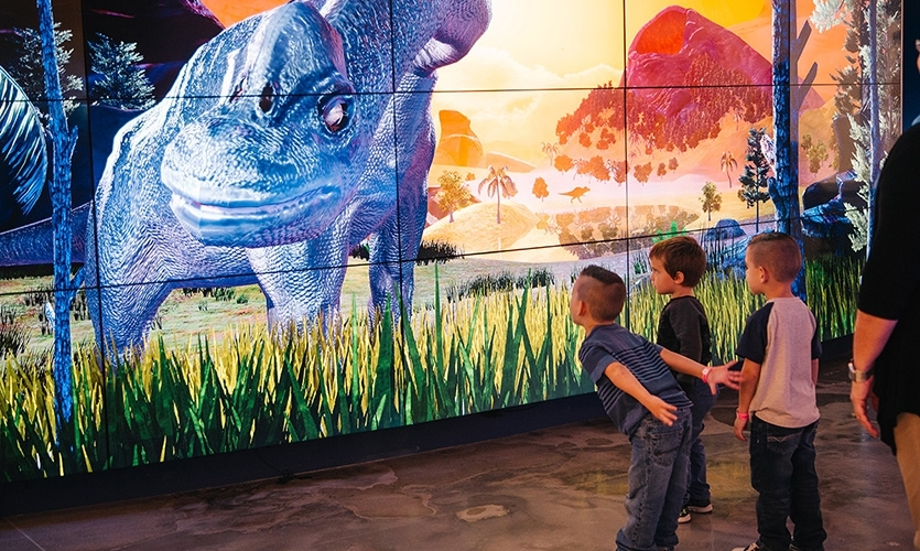 DinoStomp transports up to ten users at a time to the Mesozoic era, where interaction with dinosaurs is possible within a 3D landscape staged on a giant screen.