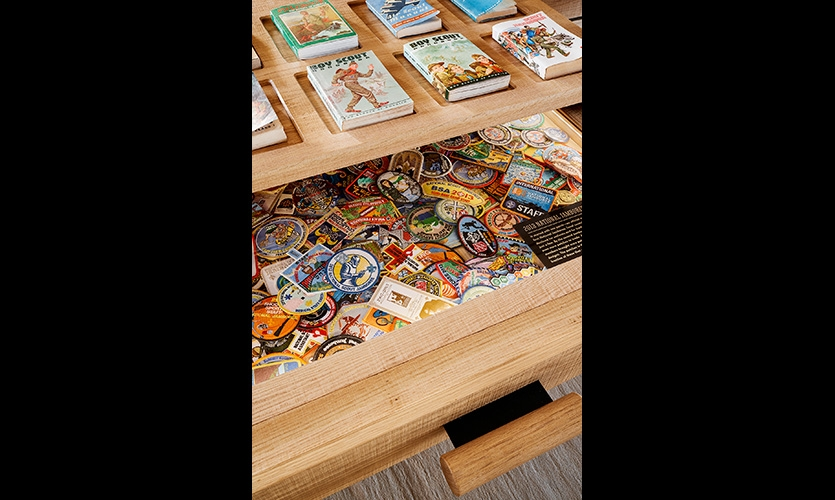 A drawer containing a sampling of the 2013 Jamboree patches created by local councils for trading with rabid collectors. Above the drawer sits a display showing the evolution of the Scout Handbook.
