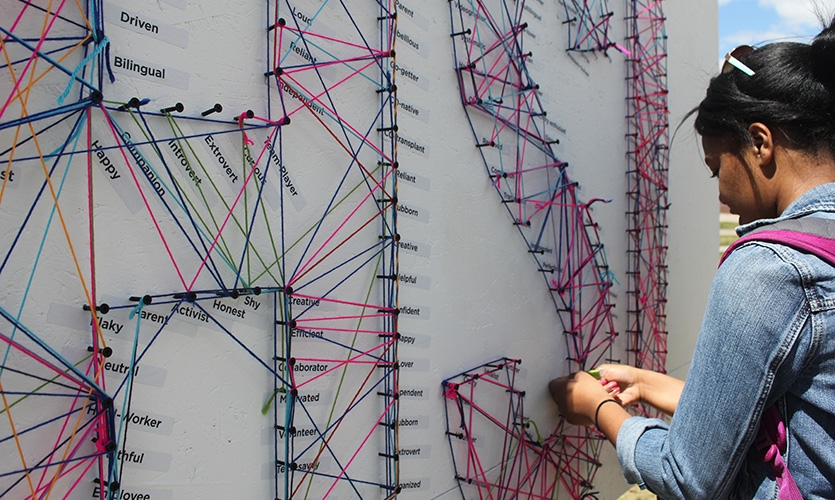 Passersby engage with their community by stringing each peg they identify with while weaving their identity and characteristics within others.