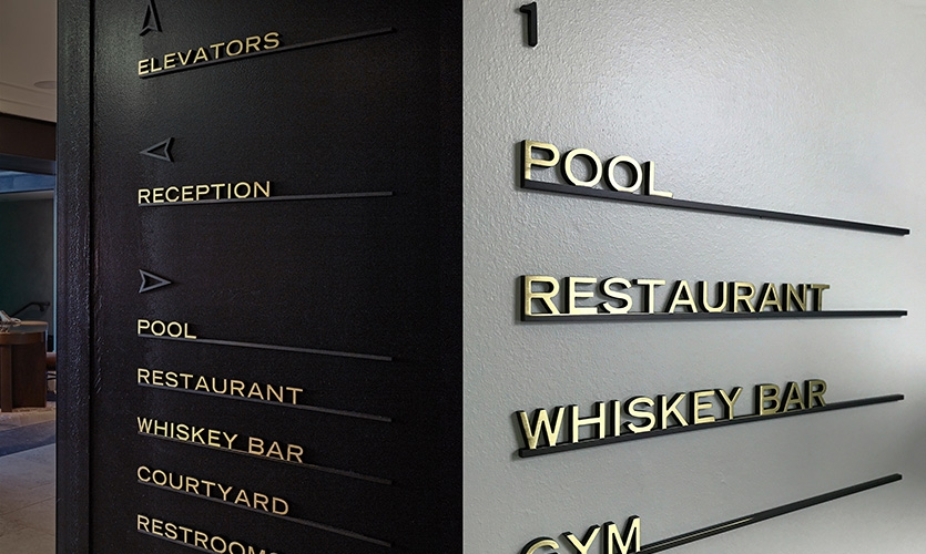 Solid brass wall directionals. Each piece was blackened, then only the letters were polished to create a rich high-contrast look.