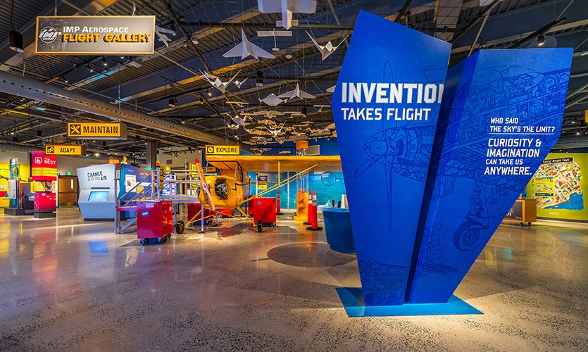The Flight Gallery welcomes visitors into a three-dimensional graphic world, where aircraft blueprints and designs come to life. The Gallery relies on aircraft hangar iconography and colours.