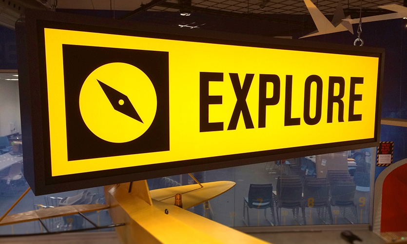 The gallery features backlit station identifiers themed to resemble aircraft hangar safety signage. These were custom designed and included a series of unique icons that relate to activities below.
