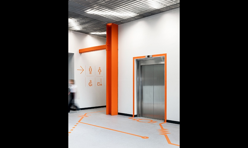 Internal wayfinding. The linear language highlights doorways while the floor is used to display the relevant electronic symbol. In this case, lifts are represented by motors.