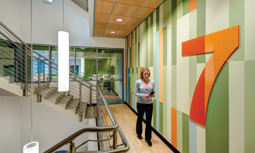 A mural graphic in an open stairway of the research facility promotes use of the stairs and supports wayfinding. (Design: Kolar Design. Architects: HDR Architecture, GBBN Architects)