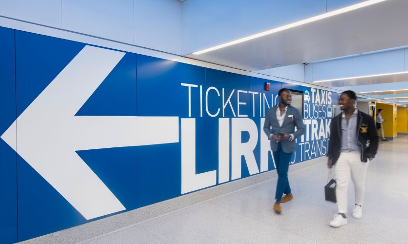 For greater visibility and pedestrian flow, the supergraphics are applied directly to the walls and columns of the concourse.