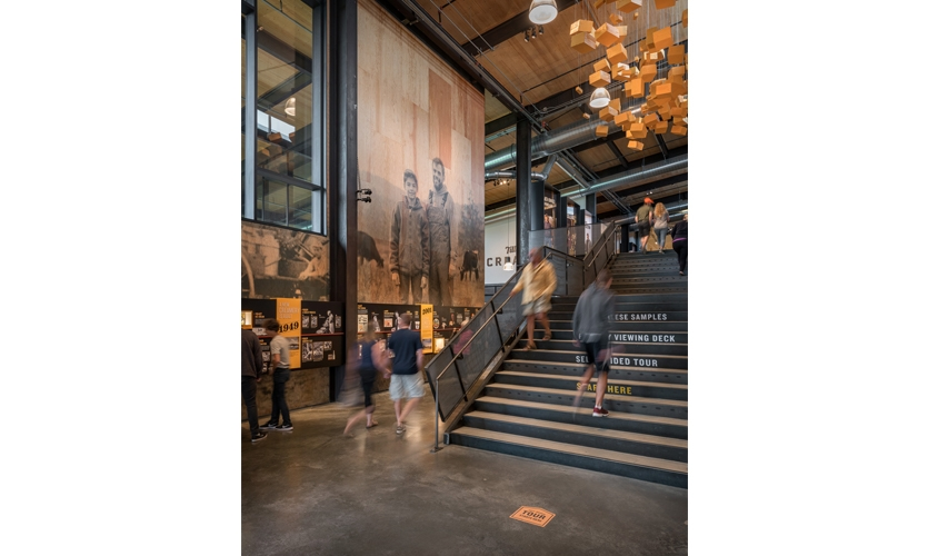 Visitors are enticed to explore Tillamook 's 110-year timeline, showcasing 30-ft tall photos of farmers past and present, or follow the floating cheese sculpture to the second floor exhibits.