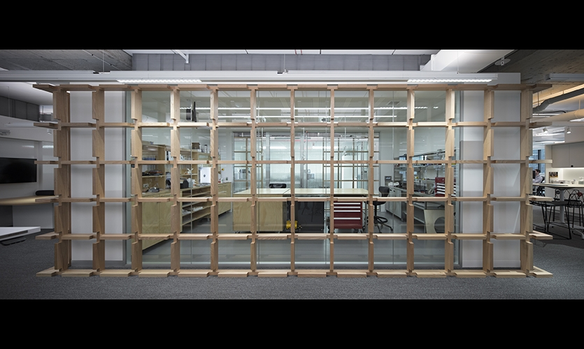 Unique timber environmental graphic installed around the digital fabrication lab reiterates 'testing grounds' theme and features a metric dashed grid that allows for easy measurement reference. (image: wooden cage around room)