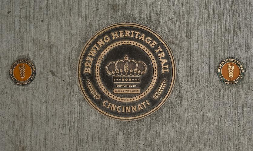 Sidewalk marker (image: bronze logomark inlaid in sidewalk)