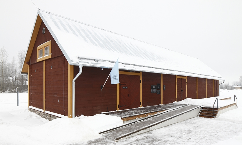 The exhibition is installed in a former baggage depository, where the design solution was dictated by the historical building's function. (image: wooden exterior of building in snow)