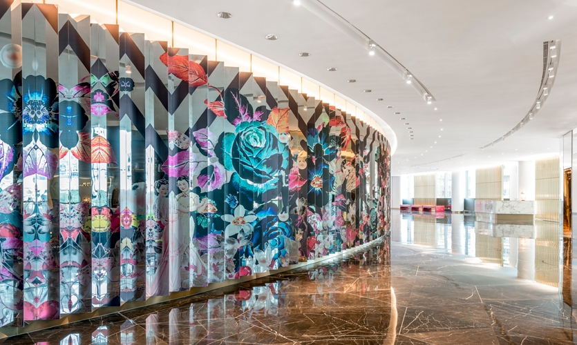 A dramatic agamograph mirror at the ballroom entry casts reflections of guests amongst Qi Pao florals.