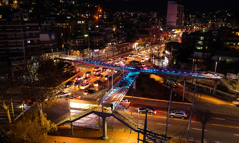 A nighttime view of the Jahadam Project. (image: overpass glowing at night with florescence)