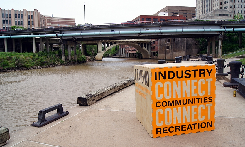 Six large cubes that featured each of the six sites of the Encounter installations lined the waterfront at the original port of Houston. (image: large wooden cube with text emblazoned on it)