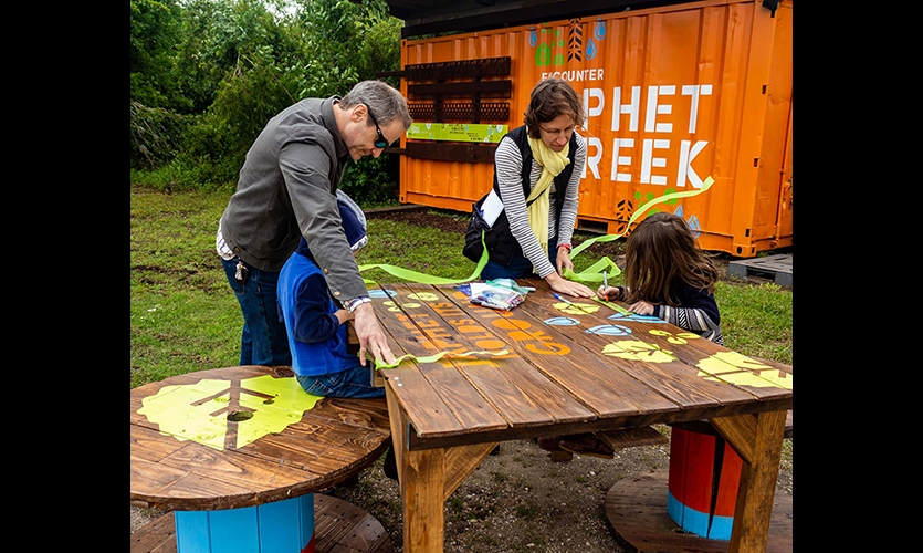 At Japhet Creek, an assortment of activities encouraged walking the trails. Installations used recycled materials whenever possible, like this repurposed container. (image: visitors around a table with graphics and in front of a shipping container)