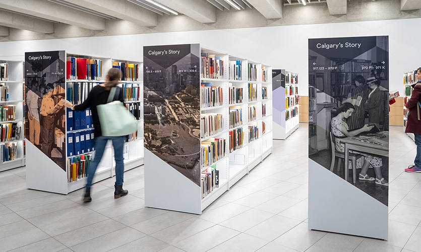 Interpretive stack ends tell the story of Calgary. (image: library shelves with printed graphic on side)