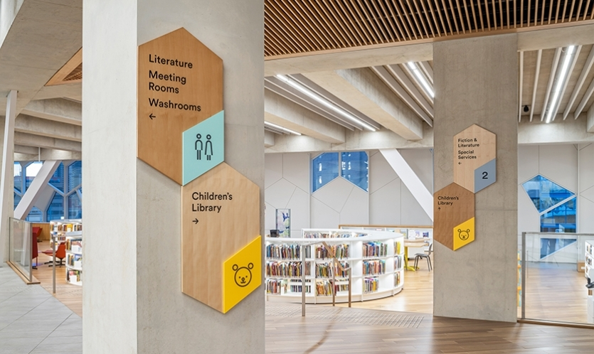 Clear and concise information alongside simple pictograms are used to achieve easier comprehension to all users. (image: wooden library wayfinding)