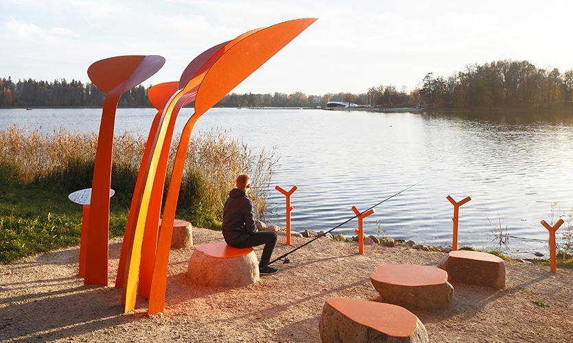 Rod holders are provided to support fishing rods, the use of stone ensures the seats' long term use. (image: man fishes from orange bench)