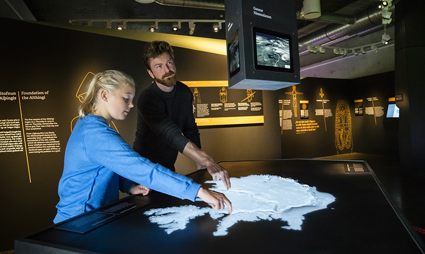 Routes to Þingvellir: In this tactile installation visitors navigate an elevated landscape of Iceland while animating their trail in a 3D view on screens. (image: visitors touch 3D map of landscape)