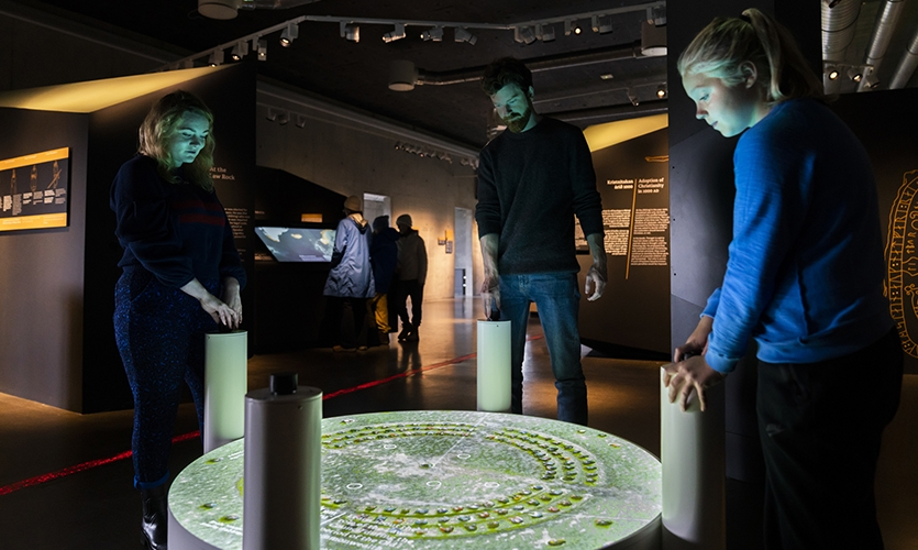 Through tactile knobs and Virtual Reality visitors can look into the past and become a part of the Law council which was a part of the General Assembly in Iceland that was founded in 930 AD. (image: three visitors at small podiums using exhibit)