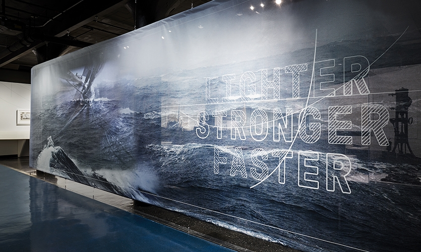 """Lighter, Stronger, Faster: The Herreshoff Legacy"" (image: title wall of exhibit featuring clean lines and boat hull design)"