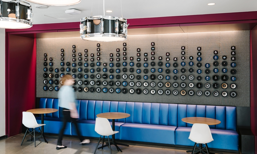 The theme of this break room is amped up with a tactile equalizer made of 203 speakers inset into a metallic cloth background.