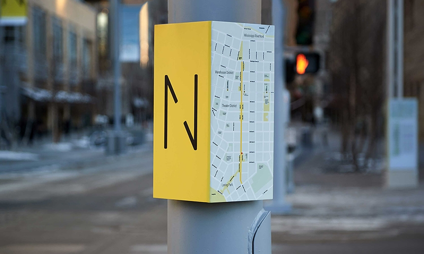 Nicollet (image: bright yellow-edged wayfinding sign with map and N logo)