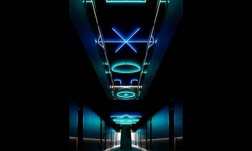 Dimly lit guest corridors are illumined by lighting installations and wayfinding representing alchemical formulas and astrological constellations