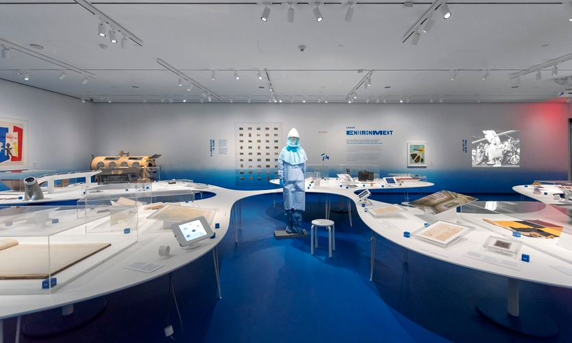The large, curvilinear table is the main organizing device for the exhibition, carrying most of its artifacts and surrounding life-size objects, such as this life-size Ebola suit.