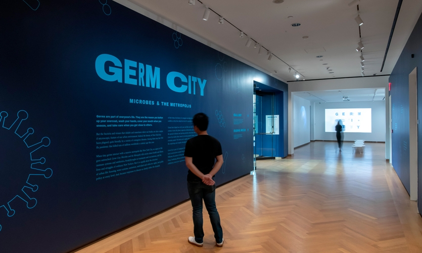 The introductory anteroom sets the tone for the exhibition with microbe illustrations, projections that invite the viewer into the space, and large display type that mimics the movement of germs.