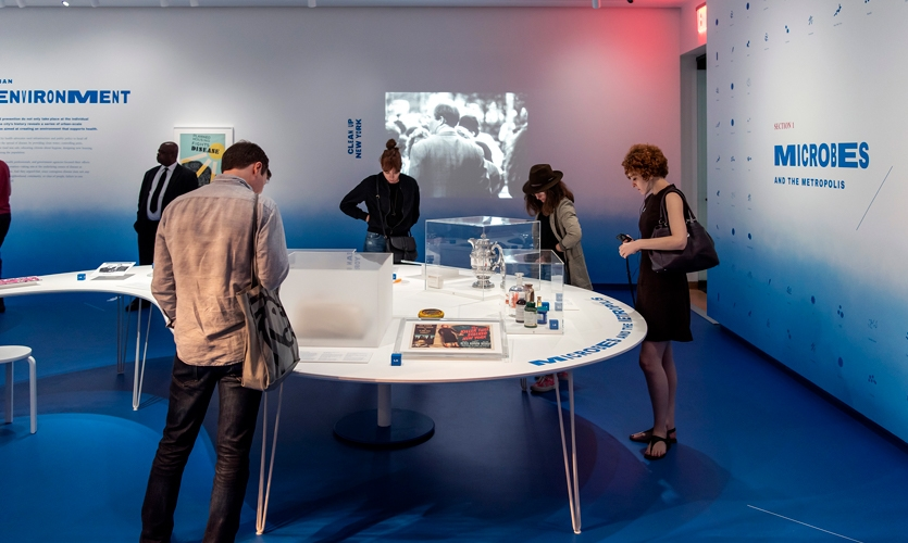 """This section, """"Microbes and the Metropolis"""" features dozens of small microbe illustrations to introduce the audience to the exhibition's """"cast of characters."""""""