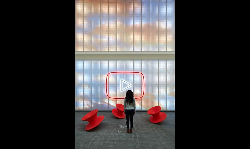 Visitor stepping on a floor medallion at center of the digital wall experience